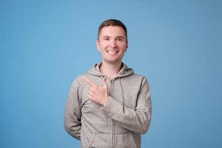 Cheerful handsome man showing direction and pointing with finger standing on blue wall background
