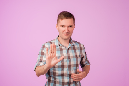 Portrait of european serious young man stretching hand towards camera with stop or hold gesture, standing against pink background. Stay away from me. I do not agree with you concept