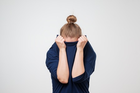 Europäische Frau versteckt Gesicht unter der Kleidung. Sie zieht einen Pullover auf den Kopf.