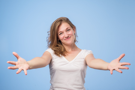 European woman raised up palms arms hands at you, isolated over blue background.