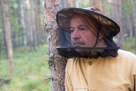 Mature caucasian man in special anti mosquito cap standing in forest and rest Zdjęcie Seryjne
