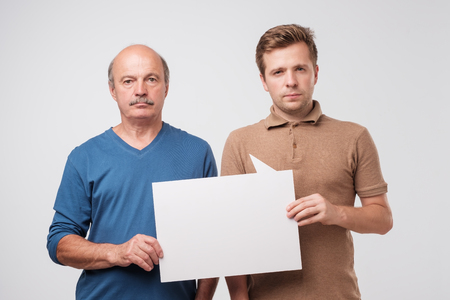 Two mature men father and son are holding a white empty billboard together. The friends are standing and smiling. Pay attention to profitable proposition 版權商用圖片