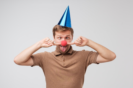 Caucasian young man with holiday cap on head and red clown nose grimacing and having fun. Concept of birthday party 版權商用圖片