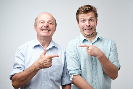 Portrait of two caucasian men pointing finger on each other. It was not me, he did it concept. Stock Photo