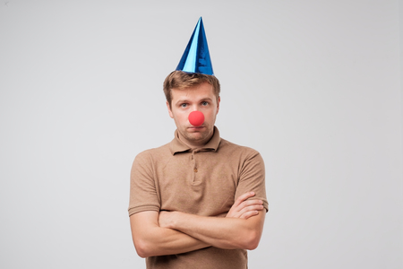 Funny mature man with red clown nose looking sadly at camera. Nobody came to his birthday party and he is offended. Stock Photo