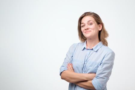 Portrait of a smiling young european woman in blue shirt standing with arms folded isolated over white background 스톡 콘텐츠