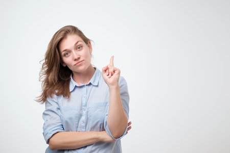 Beautiful smiling dreaming woman pointing with index finger up. Isolated over white background. Pay attention to this important information. Do not miss great sales concept
