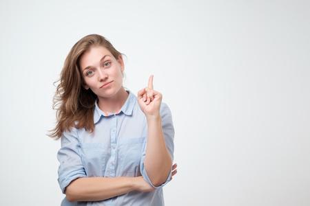 Mooie glimlachende dromende vrouw die met omhoog wijsvinger richt. Geïsoleerd op witte achtergrond. Besteed aandacht aan deze belangrijke informatie. Mis geen geweldig verkoopconcept Stockfoto