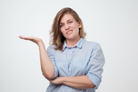 Shrugging european woman wearing blue shirt in doubt doing shrug. Confused girl gesturing do not know sign on gray background