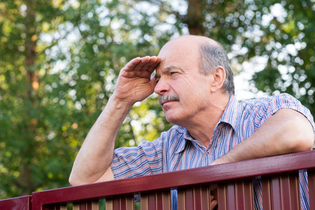 Mature caucasian man carefully watching over the fence. 版權商用圖片