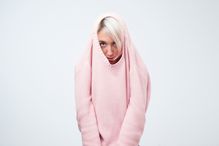A pretty caucasian girl with a social phobia hides her face in a sweater.