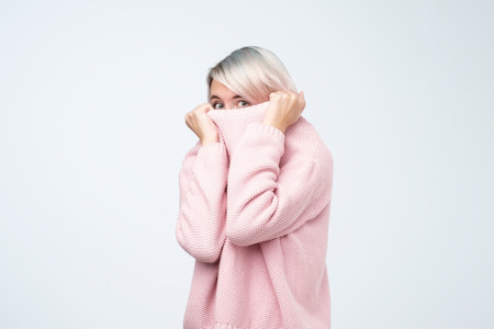 Portrait of girl pulling her pink sweater over head. Woman with scared look disappearing in her clothes Imagens