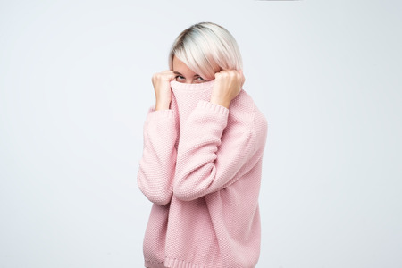 Pretty female hiding her face in warm loose sweater. Studio shot of good-looking beautiful girl wanting to stay alone