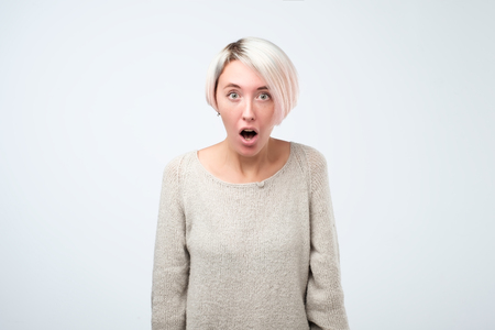 Beautiful surprised woman standing with open mouth. Human emotions, facial expression concept. Stockfoto