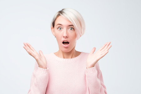 Beautiful female half-length front portrait isolated on gray studio backgroud. Young emotional surprised woman in pink sweater standing with open mouth