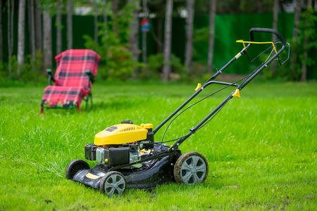 Lawn care concept. Mower standing on green grass on yard. 免版税图像