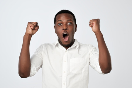 Young african man celebrating victory over gray background