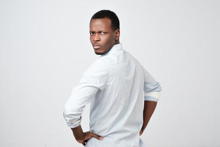 Hombre con camisa blanca mirando detrás de la cámara por encima del hombro mostrando actitud crítica. Foto de archivo