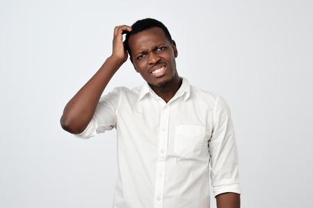 Nerveus twijfelachtig afrikaans mannetje met een verbaasde blik die een serieuze beslissing gaat nemen.