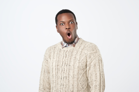 Shocked black male says wow, looks with wide opened eyes and rounded mouth 免版税图像