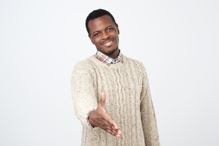 Handsome young african man in warm sweatergiving his hand for shaking 版權商用圖片