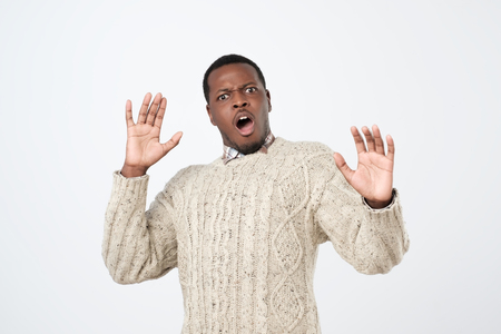 African man looking scared as noticing ghost tilting backwards and raising hands in surrender being terrified