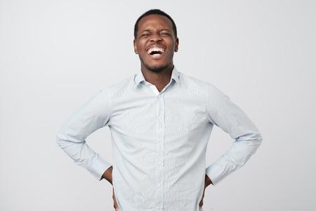Bel homme africain riant à haute voix au mème ou à la blague drôle qu'il a trouvé sur Internet, souriant largement. Banque d'images