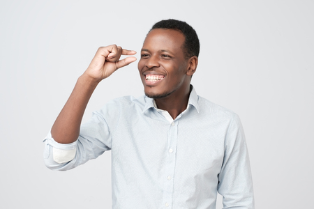 Young african man holding something small in his hands