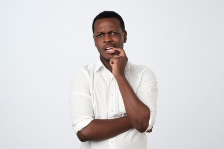 pensive serious puzzled African man touching his chin, looking thoughtful and skeptical Stock Photo