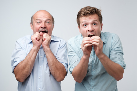 Two stunned men react on sudden news, keeps mouthes opened, stare at camera Stock Photo