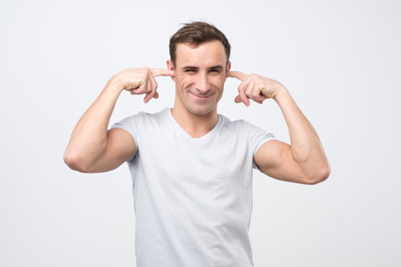 Annoyed mature italian man plugging ears with fingers. I do not want to listen to your excuses. Stock Photo