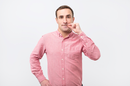 Italian young man in pink shirt doing a silence gesture. Please do not tell anybody my secret. Stock Photo