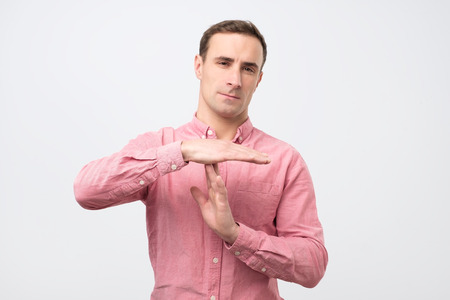 Young man in pink shirt giving showing time out hands gesture. I need a rest please.