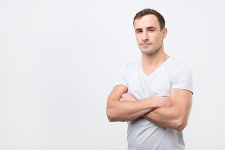 Serious young man in white t-shirt with crossed arms over gray background. Self confident guy
