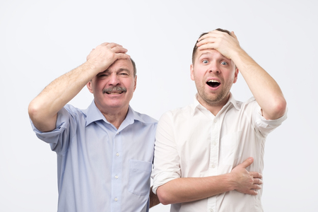 Stunned emotive two men keep jaw dropped, holding hand on head, wonder seasonal discounts and prices, stand next to each other, isolated on white background Stock Photo