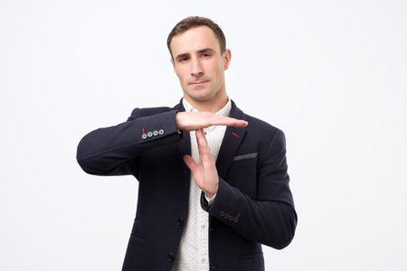 Young man in suit giving showing time out hands gesture. I need a rest please.