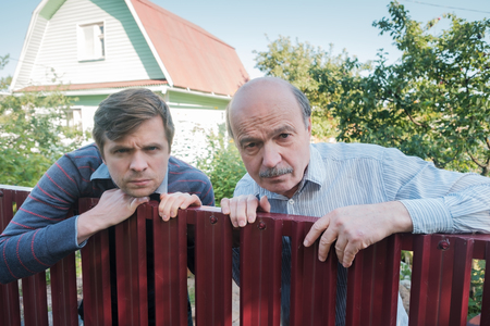 two angry caucasian men carefully watching over the fence. Concept of curious neighbors and private life 스톡 콘텐츠