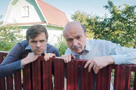 zwei wütende kaukasische männer wachen sorgfältig über den zaun. Konzept von neugierigen Nachbarn und Privatleben Standard-Bild