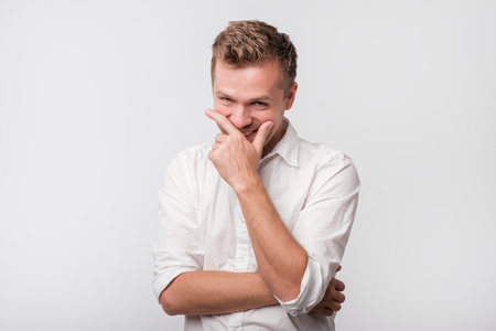 Mature man laughing and covering his mouth with hand over white background. Trying to hold a laugh not to offend some person.