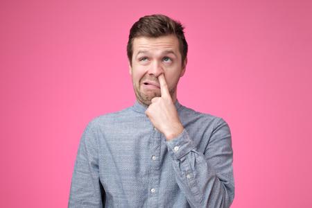 Le jeune homme européen se cure le nez. Concept de mauvaises manières.