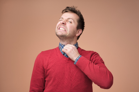 Young europeam man in red sweater feeeling uncomfortable. Colar is tight and stuffy and he tries to expand the collar to make a breath. Hate office clothes