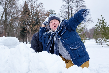 A senior man and his young son throwing a snowball, playing winter games on vacation. Stock Photo