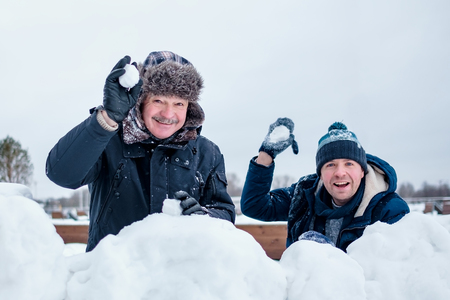 A senior man and his young son throwing a snowball, playing winter games on vacation. Banco de Imagens