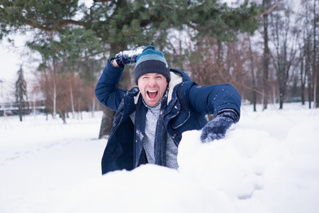 European mature man in warm clothes playing with snow outdoor. Having fun on winter vacation.
