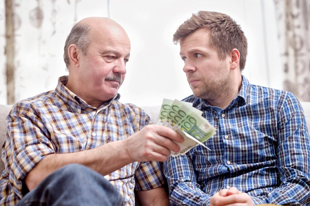 Elderly father lends money to his adult son. He helps his child deal with financial problems. Archivio Fotografico