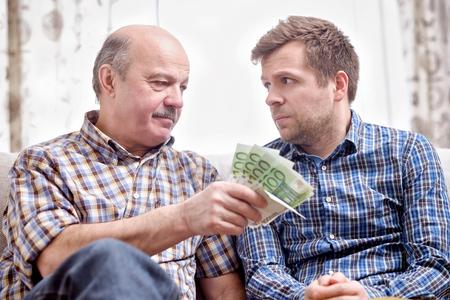 Oudere vader leent geld aan zijn volwassen zoon. Hij helpt zijn kind om te gaan met financiële problemen. Stockfoto