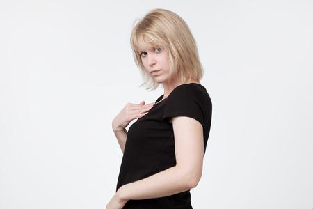 Tête d'une jeune femme se montrant elle-même se défendant verbalement, ayant une expression perplexe et perplexe sur son visage, disant Qui moi. Banque d'images