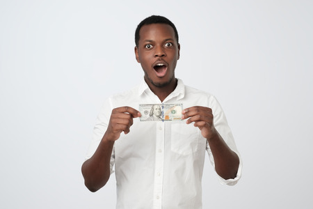 African man in white shirt is holding hundred dollars in his hands looking at the camera