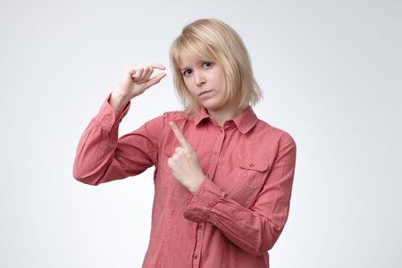 Sad beautiful positive woman, gestures shows the size of something small