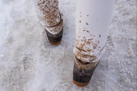 Rozpryskiwanie i topnienie kropli śniegu na białych dżinsach.